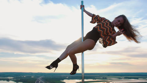 Pole dance on nature - sexy woman in swimsuit dancing on the top of dancing pole Live Action