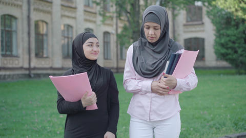 Portrait of two confident Muslim women walking on university yard and talking ライブ動画