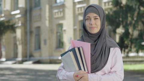 Portrait of happy Muslim woman in grey hijab posing in front of university on ライブ動画