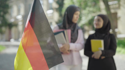 Close-up of German flag fluttering outdoors with two Muslim women talking at the ライブ動画