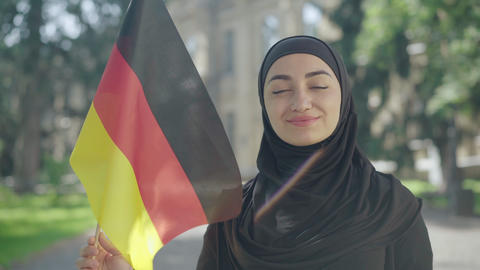 Portrait of happy smiling Muslim woman posing with German flag on sunny ライブ動画