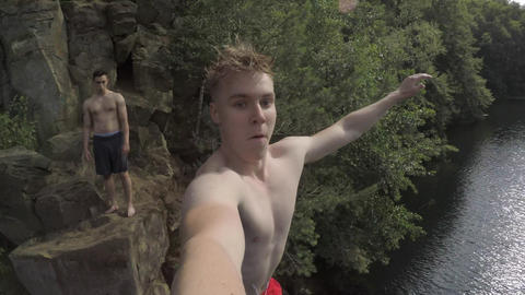 Slow Motion Action Cam Shot of Young Adult Cliff Jumping into water Live Action