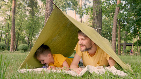 Father with son lying in camp tent. Two travelers having fun in tent. Traveling Live Action