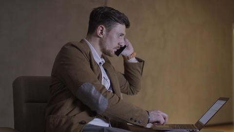 Businessman is talking on the phone while using a laptop computer Footage