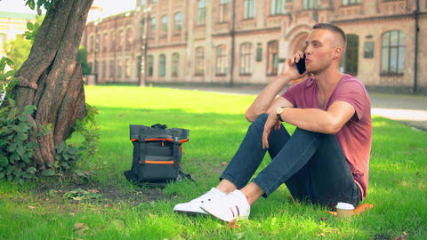 guy sits near the tree has phone conversation Live Action