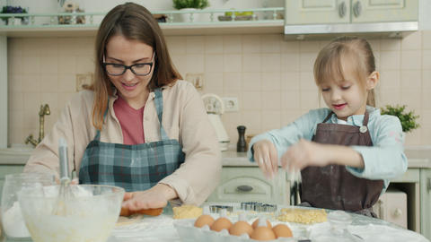 Playful kid having fun in kitchen clapping hands while mother cooking and Live Action