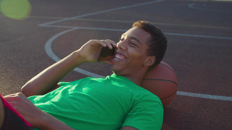 Athlete chatting on phone on basketball court Live-Action