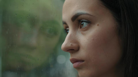 Sad woman looking out the window Live Action