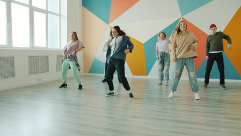 Slow motion of young people dancing in studio enjoying modern hobby together Live Action