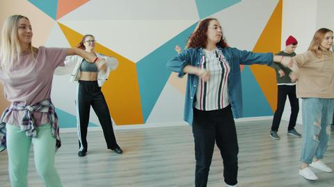 Slow motion of joyful youth dancing in modern studio together enjoying active Live Action