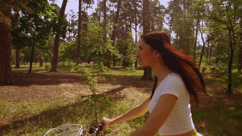 smiling girl cycling on bicycle sunlight Live Action