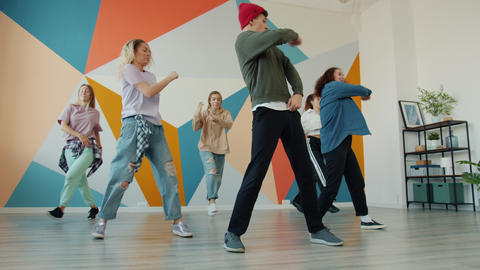 Creative youth dancing together during practive in modern studio Live Action