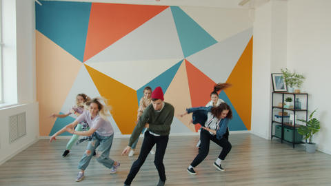 Slow motion of active youth performing modern dance during lesson in studio Live Action