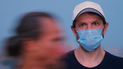 Male in protective medical facemask over city background. Man in cap and medical ライブ動画