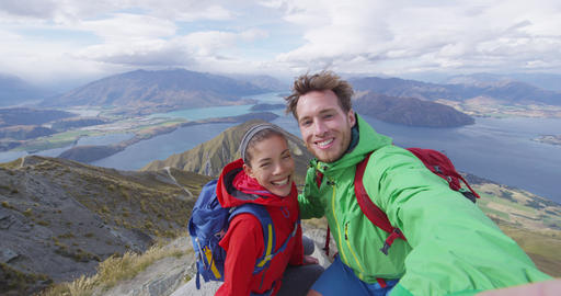 Happy couple taking selfie video on top of mountain living healthy lifestyle Live Action