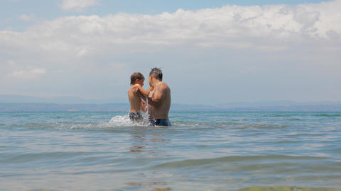 Happy european family playing at the sea. Dad and little son play and enjoy the Live Action