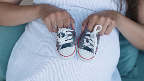 Pregnant woman holding small baby shoes ライブ動画