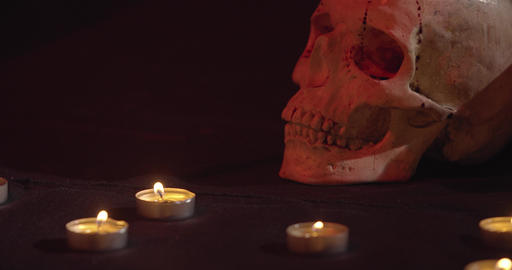 Close up of a scary skull with some blood on it, surrounded by candles, 4k Live Action