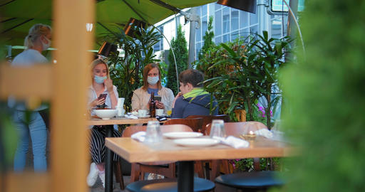 waitress in sterile gloves puts food on table with visitors GIF