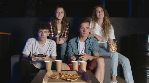 Friends console party. Two male friends winning in video game, sitting on couch GIF