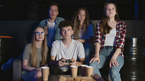 Big company of friends relaxing on living room sofa and playing video games GIF
