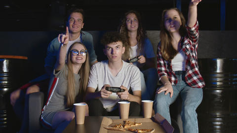 Happy group of friends playing video games at home. Man and woman are playing Live Action