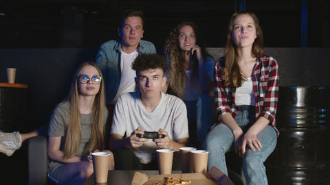 Young happy man completes hard level in video game. Having fun with friends GIF