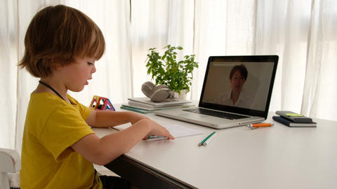 Unrecognizable child having video call with teacher on laptop indoors Live Action