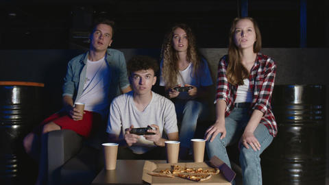 Young cheerful man and woman are having fun with video game at party in house GIF