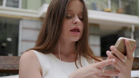 Girl with headphones sings GIF