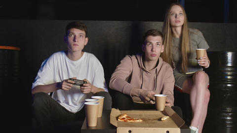 Concentrated friends playing action video game in the living room sitting on the GIF