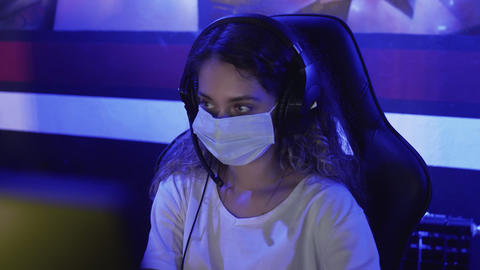 Close up of Young female Gamer in face masks plays in Video Games in Modern GIF