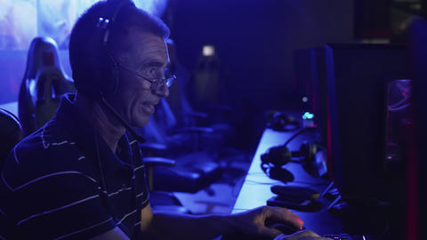Old man playing on computer late at night in Modern computer club GIF