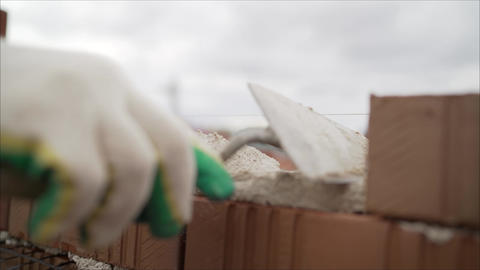Worker puts a brick wall. Bricklayer working in construction site of a brick Live Action