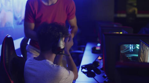 Concentrated young man sits in front of monitor and another man leaves from GIF