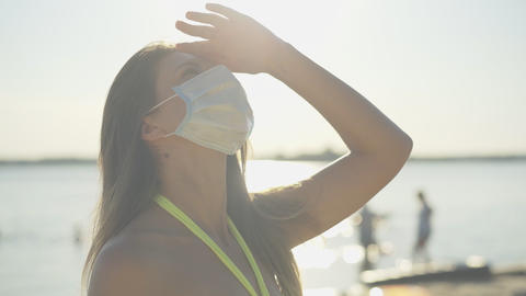 Close-up of beautiful young woman in medical face mask standing in sunlight on ライブ動画