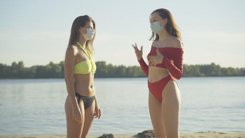 Two gorgeous tanned slim women in face masks and swimsuits talking on river bank ライブ動画