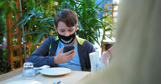 young guy in black designed face mask types on smartphone GIF