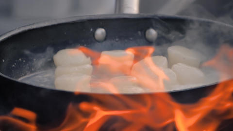 Slow motion: process of cooking scallop meat on pan at food festival Live Action