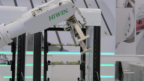 Pick and place robotic arm manipulator moving cylindrical metal workpiece Live Action