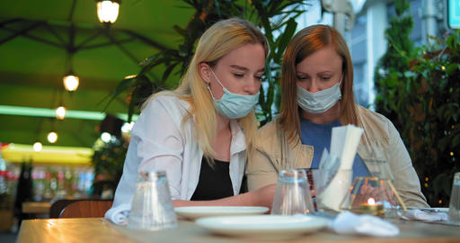 brunette and blonde in blue sterile masks sit at restaurant ライブ動画