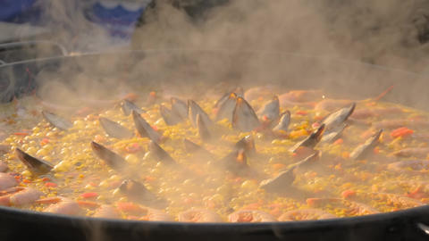 Slow motion: chef cooking paella with shrimp, mussel - close up Live Action