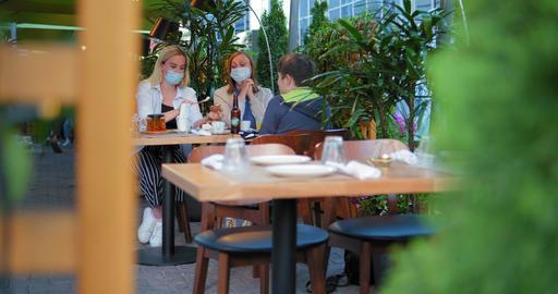 blonde gives son sandwich sitting on restaurant terrace GIF