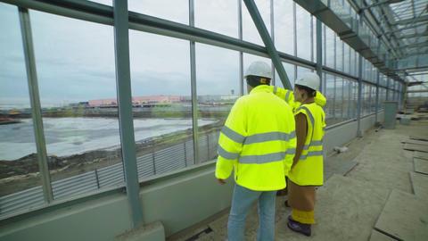 engineers check shopping mall construction site near lake Acción en vivo