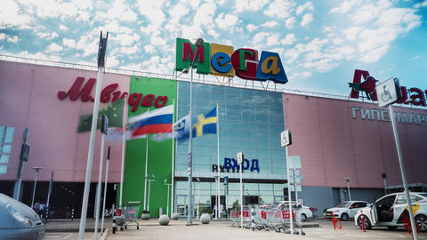 facade of Mega supermarket with flags and walking people ライブ動画