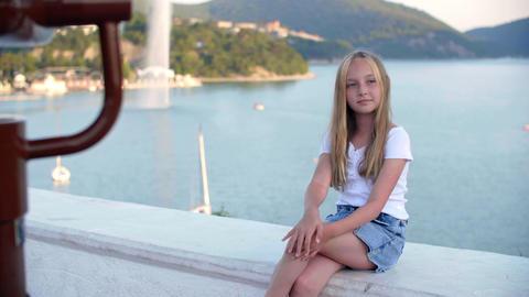 Beautiful girl sitting near sea bay and smiling at camera GIF