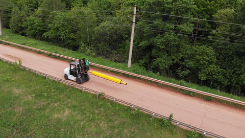 forklift loader carries yellow pipe with casing along road ライブ動画