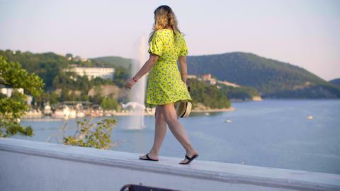 Rear view of woman walking on parapet near beautiful sea lagoon GIF