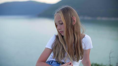 Pensive teenage girl sitting and looking down on sea coast GIF