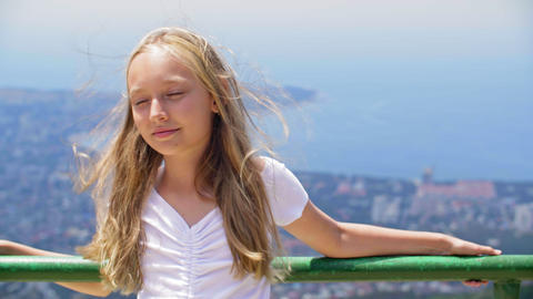 Smiling girl teenager with hair on wind standing on observation deck on mountain GIF